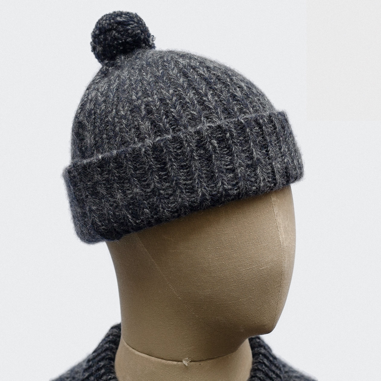 f4206929fb7 Bobble hat in lambswool tuck-stitch in navy-grey — S.E.H Kelly ...